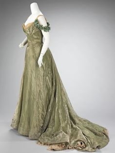 Ball Gown Jacques Doucet 1898-1900 This ball gown is simplistic in design, yet extravagant by the choice of materials used. The sheer overlayer is enhanced by the solid lamé underlayers and a sense of luxury is added by the hidden lace flounce at the hem. Undoubtedly, a woman would make an entrance in this dress, as it is extremely seductive with its form fitting silhouette and low décolleté.