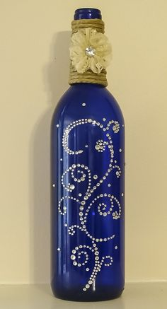 Cobalt blue wine bottle with cord, lace and rhinestone flower and rhinestone swirls - .Cobalt blue wine bottle with string, lace and rhinestone flower and rhinestone swirls - etsy cobalt blue with string tip Recycled Wine Bottles, Wine Bottle Corks, Glass Bottle Crafts, Painted Wine Bottles, Lighted Wine Bottles, Diy Bottle, Bottle Lights, Glass Bottles, Blue Bottle