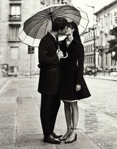 Polite kisses underneath an umbrella