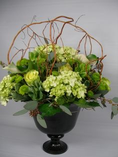 Mini green hydrangea, green beauty roses, kermit mums, bells of Ireland, anthurium, seeded euc in cage of curly willow.