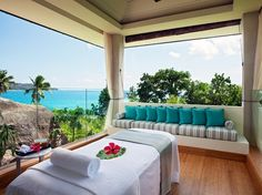 Raffles Spa, Praslin Island, Seychelles. On a luxuriantly green hill overlooking a white sand beach, a cluster of 13 thatched treatment pavilions, an open-air yoga pavilion, a lounge, and a glass-walled gym.