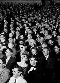 An audience in formal attire and 3D glasses watches the premiere screening of film 'Bwana Devil,' directed by Arch Oboler, the 1st full-length, color 3D (aka 'Natural Vision') motion picture, at the Paramount Theater, Hollywood, California, November 26, 1952.