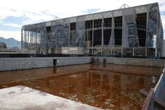 Translucent tapestries created by the Brazilian artist Adriana Varejao fall from the exterior of the aquatics centre as a combination of mud, rainwater and dead insects have contributed to the rust colour of the water in a practice pool within the competition complex created by the state for the 2016 Summer Olympics in and near Rio de Janeiro, Brazil, 2017, photograph by Pilar Olivares.