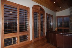 """Custom 4 1/2"""" stained knotty alder shutters in living room in Muth Valley. www.sandiego-shutters.com"""