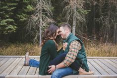 fall engagement shoot outfit idea - plaid, hunter green, jeans, sweater, and puffy vest