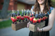 Step up a basic fruit platter by serving a variety of fresh berries on skewers and displayed on wood serving blocks.