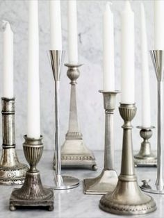 Inspiration: Unique Collection Displays. Group of antique candlesticks in a variety of shapes and sizes to create a less formal setting.