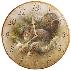 "Beautiful clock featuring a squirrel in the pines by Rosemary Millette. This clock measures 11"" round. Made of high quality precision quartz movement. Requires 1 - AA battery not included."
