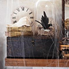 Use elements that aren't typical Halloween decorations for a nontraditional and eclectic mantel. Place an old seashell on top of antique books for a hint of vintage style. A blackbird under a glass cloche and cobwebs are easy touches to finish off the display./