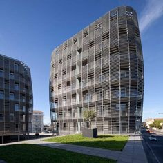 """Residential Architecture: Housing in Sète by Colboc Franzen & Associés: """"..ArchitectsColboc Franzen & Associéshave masked the facade andbalconies of three apartment blocks in the south of France behind curved galvanised-steel grids..Located in theport town ofSète, the three towers are connected by a podium that conceals a large undercroft car park behind a row of shops..The two eight-storey towers are filled with private apartments, while the smaller six-storey block contains social…"""