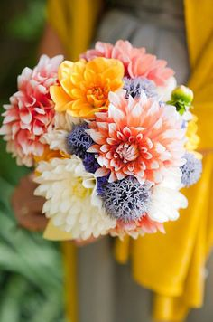 A bouquet of dahlias, in shades of orange and yellow, is reminiscent of a dazzling sunset.