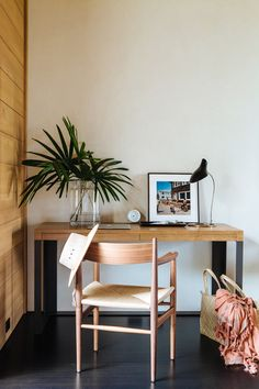 Small wooden desk in white-walled room.