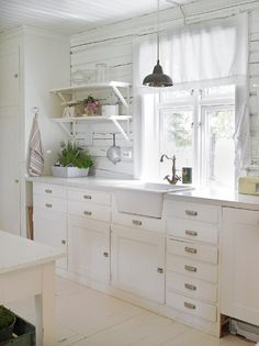 A simple white kitchen is given rustic charm using old painted white boards and open shelving.