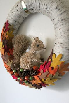 A cute squirrel wreath, with a yarn and felt base, large squirrel, felt oak leaves and pinecones, 14-inch size. Celebrate fall with this adorable squirrel wreath! Ive wrapped a 14-inch straw wreath form with tan flecked yarn. Ive stood a large sisal-type squirrel in the bottom, and all around him is a bed of handcut felt oak leaves in harvest colors. Hes holding a tiny pinecone in his paws, and a few more have fallen at his feet, tucked in with a few glittery orbs in orange, green, and…