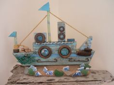 One of my driftwood boats which I decorated with curtain rings and old rusty bits and bobs. Used sea glass and broken pottery for a Sea effect. By Philipppa Komercharo.