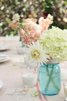 Courtney's discussion on Hometalk. Summer Table Setting With Blue Mason Jars - A simple summer table set with blue mason jar centerpieces and cottage flowers Color Splash, Blue Mason Jars, Shabby Chic, Outdoor Coffee Tables, Mason Jar Centerpieces, Vases, Centerpiece Ideas, French Country Cottage, Country Living