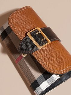 A Burberry continental wallet in textured leather and English-woven House check. The design has a regimental belt detail with a polished gold metal buckle referencing the trench coat.