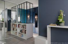 Les clients souhaitaient ouvrir la cuisine sur l'entrée de l'appartement. Un espace bureau a été conçu dans un cagibi existant. L'idée était de travailler avec des camaïeux de gris en adéquation avec un sol en grès cérame pour apporter un côté moderne à l'espace. La cuisine en laqué blanche et bois clair se veut fonctionnelle et contraste avec les murs gris anthracite.