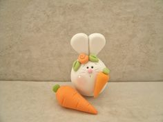 A whimsical little bunny and two carrots created from polymer clay. (This is 2 pieces). This is an original and handcrafted design. The bunny stands approximately 1 3/4 tall. All parts have been secured with liquid polymer for increased strength and both pieces were lightly
