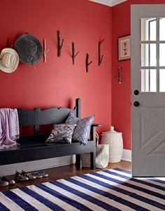 red wall. rug. branch hooks. seating. aaand the hats too.