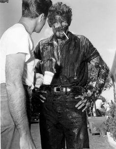 James Dean the Giant taking a break from the movie Giant while covered in oil