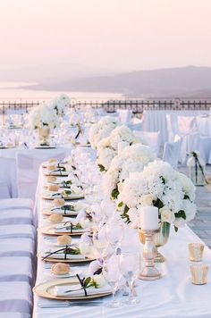 A single white rose on each plate with small arrangements of white roses and hydrangeas running down the table is simply lovely.