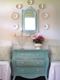I love the color, the idea of having a dresser between 2 chairs or beds and a matching mirror above it.  cute!