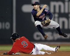 Minnesota Twins shortstop Brian Dozier completes a double play while avoiding sliding Boston Red Sox's Mike Aviles during the fourth inning of a baseball game at Fenway Park in Boston, Friday, Aug. 3, 2012