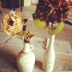 Easy wine bottle art! Scrape off bottle labels, puff paint word(s), let dry, spray paint 2 coats (I used Almond color), spray with matte protectant, embellish how you wish (I used hemp string with glue to wrap around the neck of the bottle and bought the flowers from Michael's)!!!!