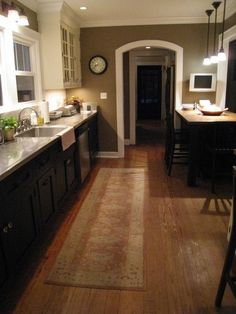 white upper and black lower cabinets, wall colors, recessed lights, hanging lights, wood floor