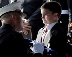 Eight-year-old Christian Golczynski accepts the flag for his father, Marine Staff Sgt. Marc Golczynski, during a memorial service. Marc Golczynski was shot on patrol during his second tour in Iraq (which he had volunteered for) just a few weeks before he was due to return home. http://www.HireaVeteran.com
