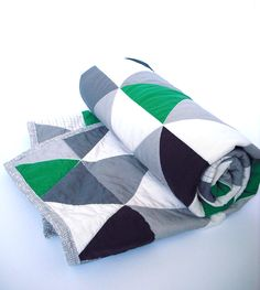 The green in this beautiful handmade baby quilt is the perfect pop of color. You can easily design a stunning nursery scheme around it. Featuring a beautiful modern triangle fabric exclusive to NotSewStrange. The 100% eco-friendly cotton print has a contemporary combination of Kelly Green, shades of grey,black and white triangles. Super soft and warm, it has been machine quilted following the triangles. The reverse side features a grey crosshatch in 100% cotton quilter fabric with a grey…