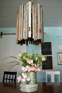DIY vintage wagon-wheel reclaimed wood chandelier and fresh flowers in Norah Vases from Accent Decor #mismatched chairs #barndoor #chalkboard #DIYchandelier