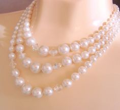 Ce bel mid century bavoir collier est composé de trois rangs de perles graduées simulés accentués avec des perles luisantes d'aurore boréale.  Les perles sont gradués de 4mm au milieu du dos à l'avant centre de 12mm.  Dimension (s): 18 Long (y compris les extensions, qui peuvent être utilisées pour ajuster la longueur).  Conclusion : Berger crochet, perles Extensions.  Très bon état !  Voir http://www.etsy.com/shop/JoysShop?ref=pr_shop_more pour supplémentaire vintage...