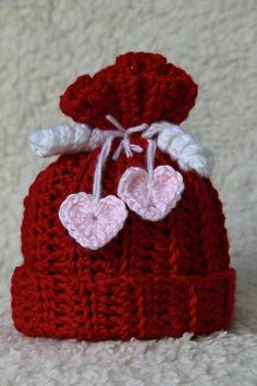 SWEETNESS IN RED BABY GIRLS HAT This little Red Crochet Hat has a turned Up brim on the bottom, White Curly Cues, & Pink Crochet Hearts. Its just