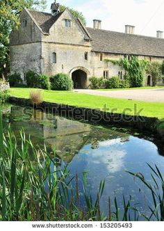 Old English Manor House Surrounded by a Moat - stock photo
