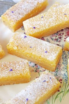 Lavender Lemon Bars - close-up of lemon bars with powdered sugar and lavender buds sprinkled on top | From SugarHero.com