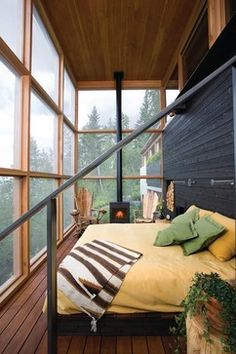 Modern yet rustic sleeping porch. The small fireplace is genius. And, I love the screened panels!