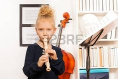 music: Blond curly girl plays flute standing near the cello in musical school
