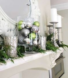 Glass container filled w/ ornaments, mercury glass votives, spray painted thrift store candle sticks + greenery = affordable beauty.