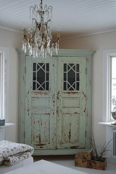 "Great DIY idea...make a custom corner cabinet from 2 old doors & molding....Perhaps it's only a facade that reveals shelving behind ... top shelf holding a lighted vignette of baskets appearing to be the top of the ""cabinet""."