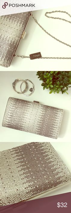 """Natasha Silver Crystal Clutch Beautiful sparkling silver clutch instantly dresses up an evening outfit.  Rhinestones on front, smooth silvery fabric on back. Opens about 2 1/4"""" with elasticized fabric siding to keep everything inside. On very close inspection can see and feel a little glue from the rhinestones along the edges (see last pic), has an odor which will hopefully go away when aired out (I kept in packaging except for photos). Measures 8 3/4"""" x 4 1/2"""" 1 3/4"""". Comes with a 46""""…"""