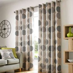 Crafted from quality cotton and available in a choice of sizes, these patterned eyelet curtains feature a textured geometric circular design in natural and char...