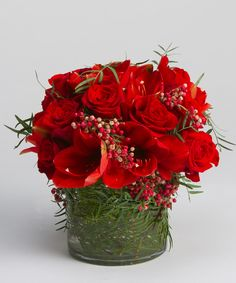 Mistletoe - A lush collection of reds, including roses, amaryllis and pepperberry, with fern accents in a cylinder vase - a new twist to a timeless tradition. #robertsonsflowers #christmas #flowers