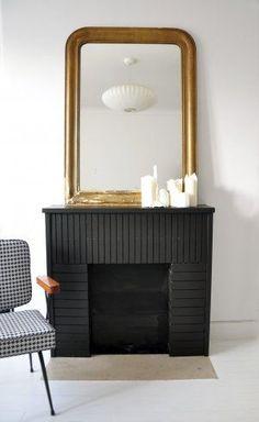 Une cheminée en brique repeinte en noir carbone dans un esprit industriel, magnifié par un miroir