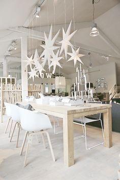 Tolle Esszimmer Einrichtungsidee besonders zu Weihnachten schön. Holz Esstisch mit Sternen als Leuchten und modernen weißen Stühlen.