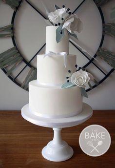 Beautifully elegant white wedding cake decorated with sugar roses and sage tinted leaves. #whiteweddingcake