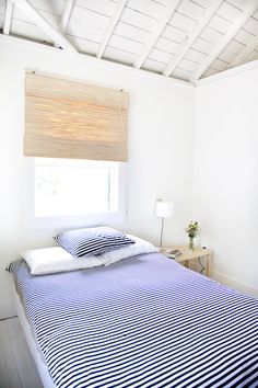 The exposed whitewashed ceiling beams really open up this bedroom - Canadian Cottage : Remodelista