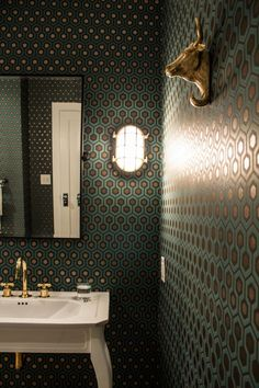 The bathroom's teal-and-gold hexagonal-patterned wallpaper adds a lively vibe to the transitional space, while a white pedestal sink adds a traditional touch. Towel hooks featuring gold bull sculptures hang on the wall, providing an eclectic, funky edge.