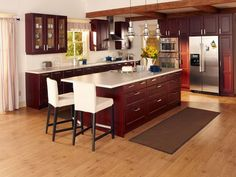 Cherry Wood Kitchen Cabinets, White Countertops, White Armless Chairs, Metal Chandeliers, and Rectangular Rug for Beautiful Kitchen Design